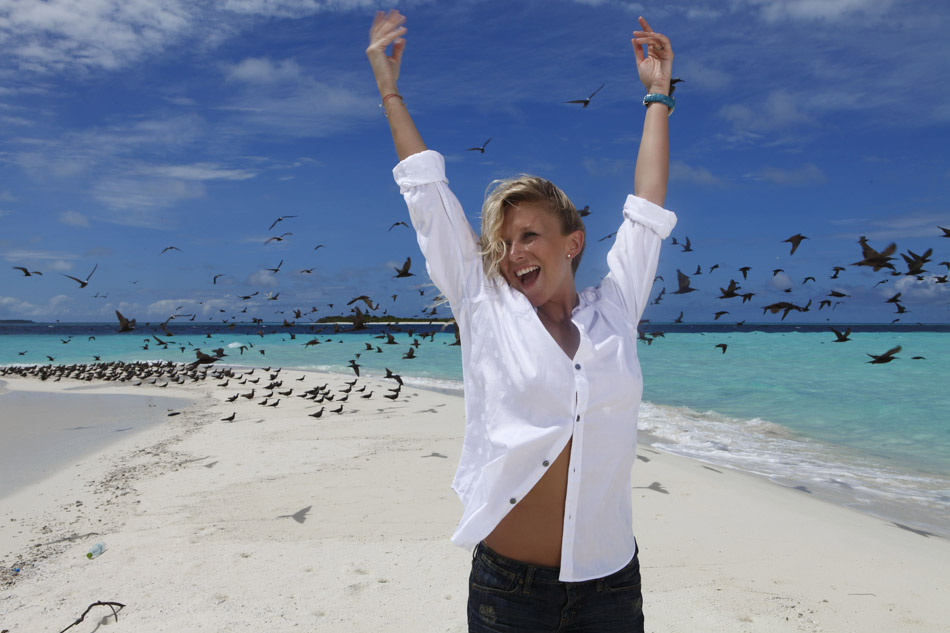 Julie Taton l'animatrice à RTL-TVI et TF1 et l'émission Secret Story, la belle femme souriante sur la plage du Kanuhura aux Maldives.