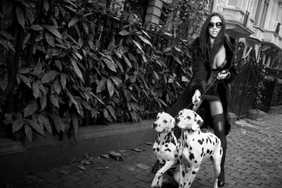 Photo en noir et blanc d'une belle femme sexy en lingerie dans la rue en porte-jarretelles avec ses deux dalmatiens.