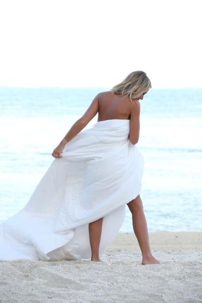 Julie Taton nue sur la plage dans une couverture